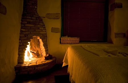 emanating: Warmth emanating into a small rustic bedroom, from the blazing fire in a rugged stone fireplace.  Stock Photo