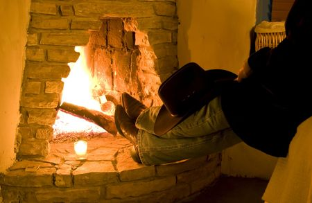 stone fireplace: A person sitting with their boots resting on the hearth of a blazing rustic fireplace.  Stock Photo