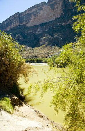 View from the bank of a river with green colored water and high looming cliffs.  photo