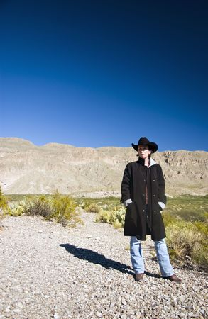 cowgirl boots: A woman dressed in a black coat and black western hat observing her surroundings.