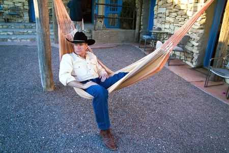 Un hombre vestido con un sombrero de vaquero y botas de descanso en una colorida hamaca.  Foto de archivo - 2011456