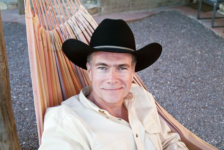 A smiling man with beautiful green eyes wearing a cowboy hat and resting in a hammock. Banco de Imagens