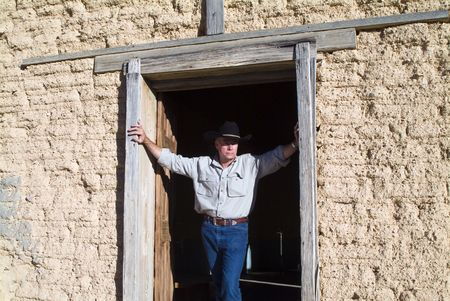 A man with wearing a cowboy hat standing in the door of an old weathered adobe building.
