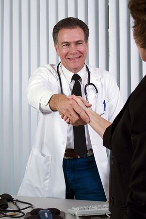 approachable: A man dressed in a lab coat with a stethoscope around his neck shaking a womans hand.