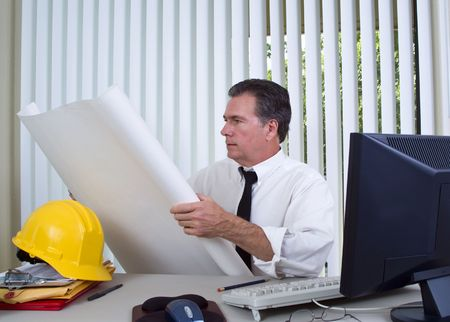 A man sitting at a desk with a computer and a hard hat holding a large rolled out paper.