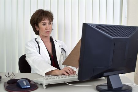 A woman dressed as a doctor working on a computer.