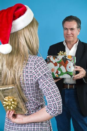 A woman in a Santa hat handing a man a gift while holding another behind her back.