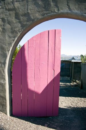 A rustic, arched entryway with the door freshly painted bright pink.  photo