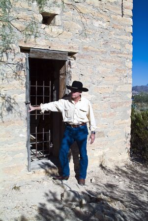 jailer: A man in western attire standing outside an old ruin of a jail
