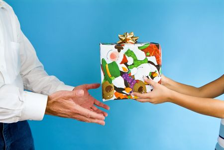 giver: A child handing a boxed wrapped in Christmas paper to a man acting as the recipient.
