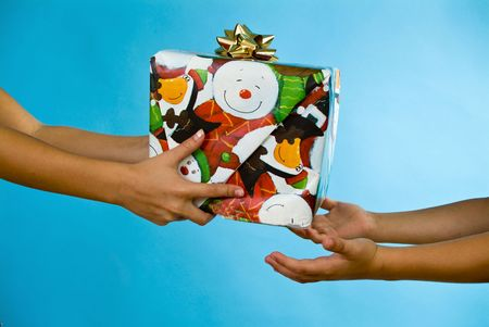 giver: A child in the act of giving what appears to be a Christmas gift to another child.  Stock Photo