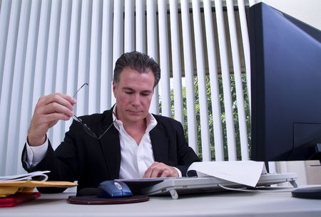 A man sitting at a desk pouring over a document he has in front of him.  Standard-Bild