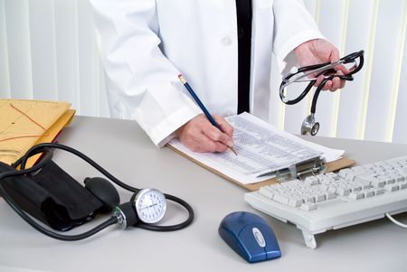 devise: A woman holding a stethoscope; standing by a desk with a blood pressure cuff laying on it.