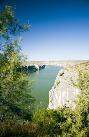 enveloped: A wide green river bodered by rocky cliffs and enveloped in a bright blue cloudless sky.  Stock Photo