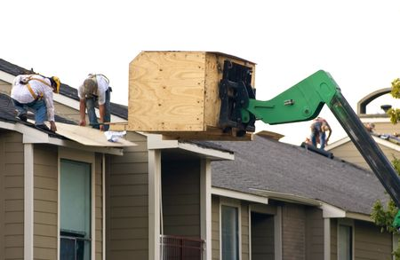 A group of workers repairing the roof of an apartment complex.  Stock Photo