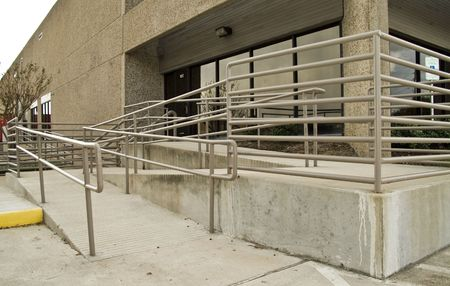 rámpa: The front of a building equipped with a ramp and railings for the physically challenged.