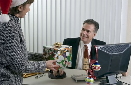 appears: A woman in a Santa hat giving what appears to be a co-worker a Christmas gift.