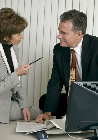 A man and a woman in an office setting appearing to be co-workers engaged in discussion.  Imagens