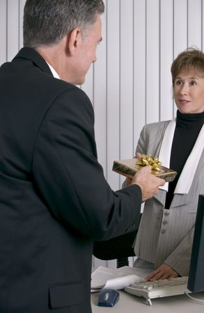 A man handing an employee or co-worker a Christmas Gift.