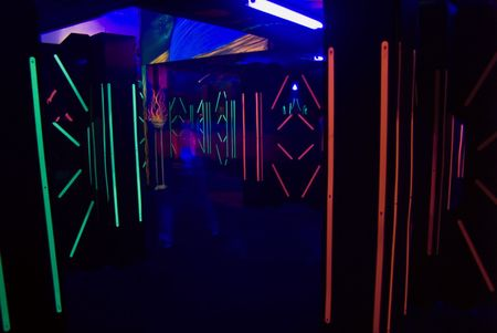 The colorful florescent lights of a laser tag room with a blurred laser tag player.