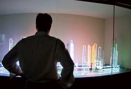 the explanation: A man standing in front of a colorful exhibit in a natural science museum.