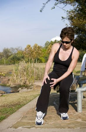 A woman jogger holding her knee as if in pain.