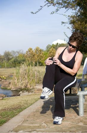 grasp: A woman sitting on a park bench grasping her knee as if injured.