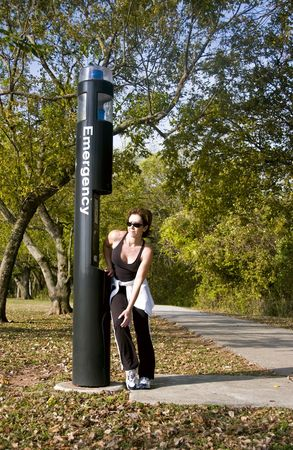 A woman standing by an emergency call box holding her knee as if in pain. Stock Photo