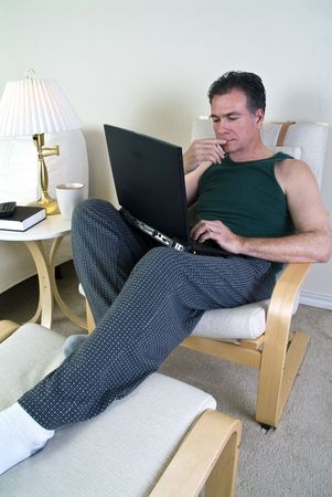 lap top: A man in pajamas with a lap top in his hand and a pensive look on his face.  Stock Photo