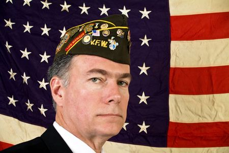 A man wearing a V.F.W. cap standing in front of an old faded 48 star U.S.A. Flag.