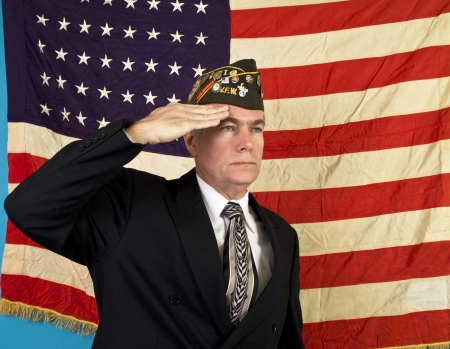 A man in a VFW cap saluting and standing in front of an old faded 48 star American flag.