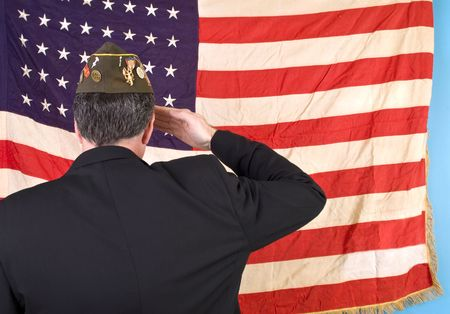 salute: A man in a VFW cap saluting an old faded 48 star American flag.  Stock Photo