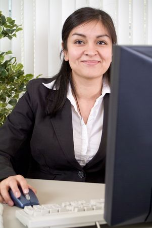 upwardly mobile: A young woman with a friendly smile on her face sitting at a desk or workstation.