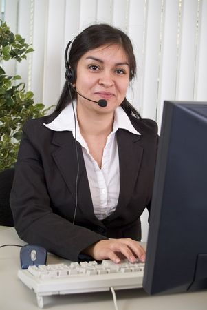facilitate: A young woman wearing a headset sitting in front of a computer monitor.