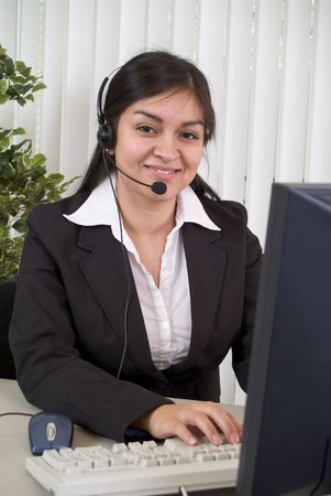 helpdesk: A young woman in a headset, smiling graciously while working the helpdesk.  Stock Photo