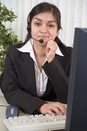 facilitating: A young woman with an amused expression on her face working the helpdesk.