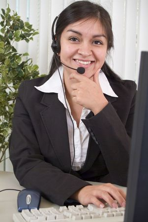 helpdesk: A coy or shy young woman manning a helpdesk wearing a headset. Stock Photo