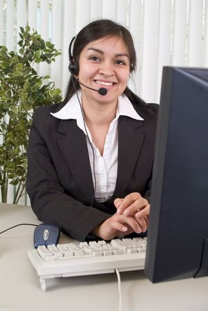 facilitate: A young woman with a charming smile, working the helpdesk.