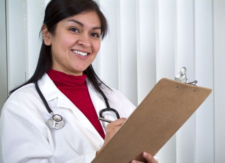 A young woman dressed as a medical professional writing something on a clipboard. Stock Photo