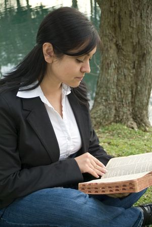 appears: A young woman sitting outside reading or studying what appears to be a bible.