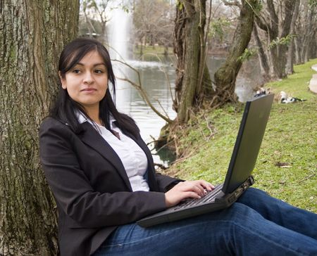 A pensive young woman with laptop computer, sitting by a small lake. photo