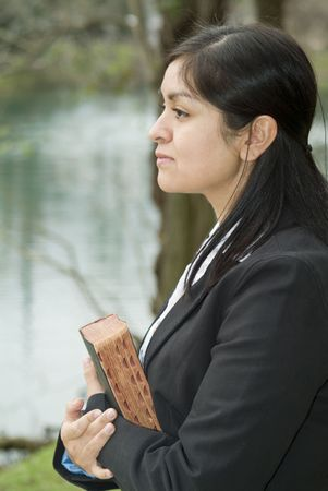 appears: A young woman gazing into the distance, holding what appears to be a Bible.