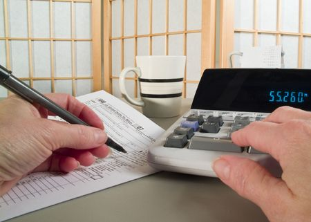 adding: A womans hands holding a pen and working with a tax form and adding machine. Stock Photo