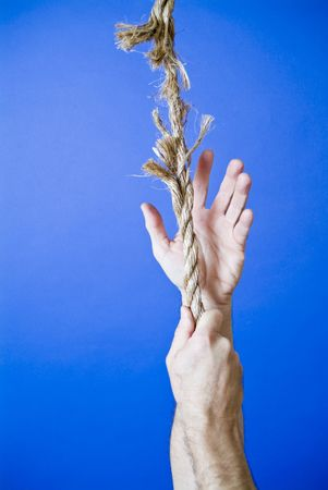 frayed: A mans hands grasping or climbing up a frayed rope portraying a very precarious situation.  Stock Photo