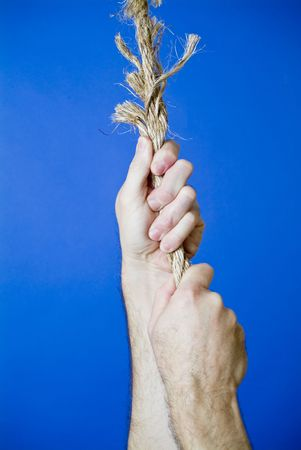 A mans hands grasping a frayed rope portraying a very precarious situation.