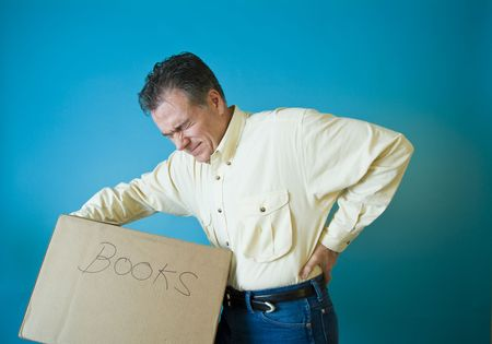 A man grimacing as if with back pain from lifting a box filled with books.