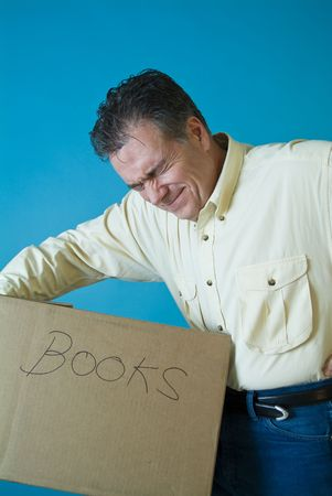 A man grimacing as if with back pain from lifting a box filled with books. photo
