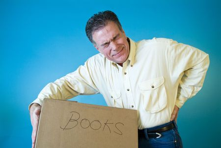 lifting: Een man met een grijns op zijn gezicht bedrijf zijn rug alsof gewonden als gevolg van de opheffing van een doos met boeken. Stockfoto