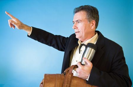A man with a briefcase and coffee mug in his hand acting as if hailing a cab with the other hand. photo