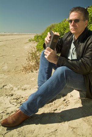 A man holding a bible, sitting at the edge of a sand dune.  Imagens
